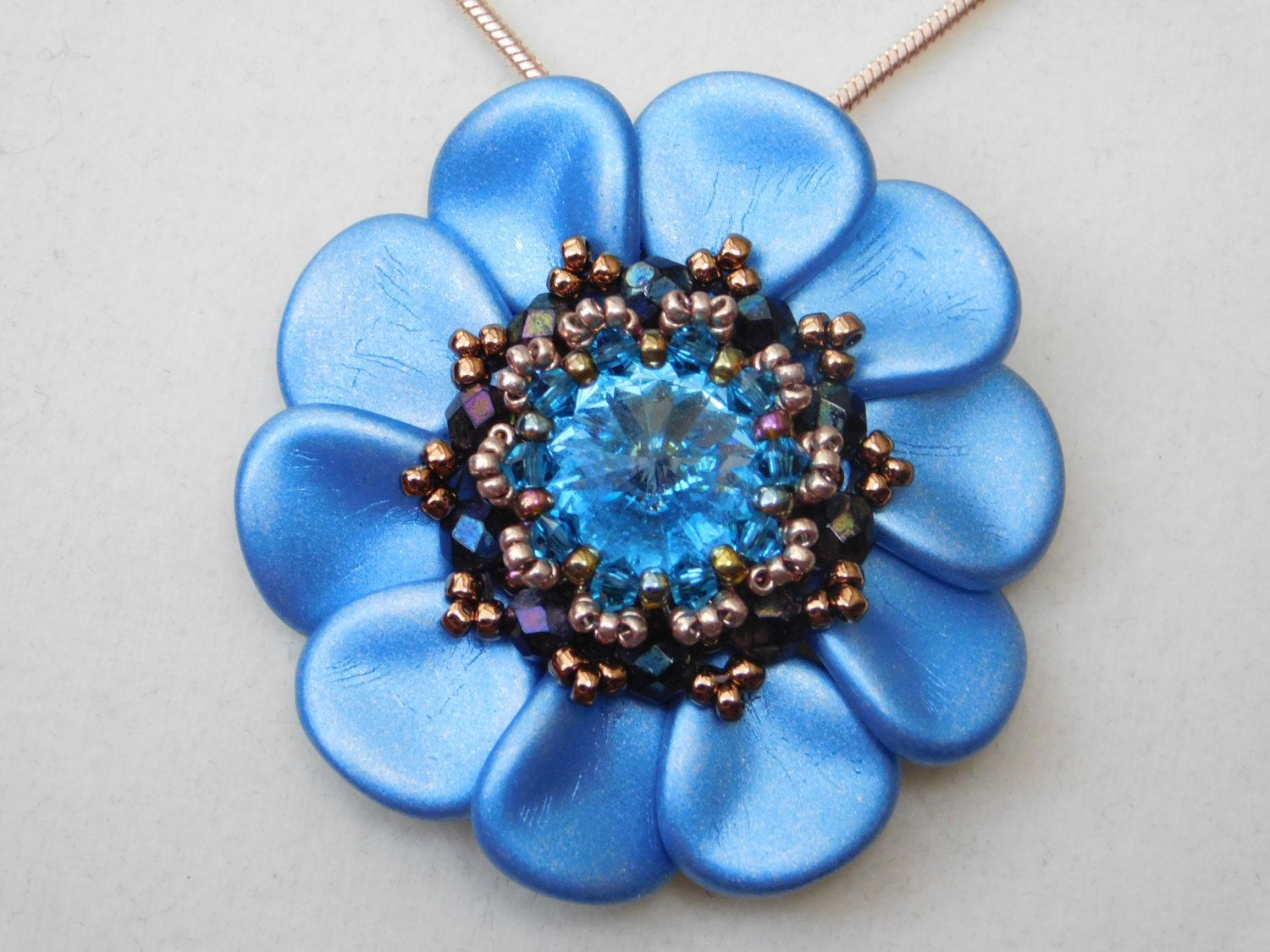 Elizabeth Pendant Tutorial  This pendant reminds me of art deco jewelry, one of my favorite jewelry styles. It features a sparkley rivoli center surrounded by petal leaves. The tutorial has step by step photos and instructions to guide you through the beading process. This listing is for the tutorial only, no finished product is included. Knowledge of right angle weave is helpful with this tutorial but the pictures show step by step how to put the pendant together. The finished pendant is…