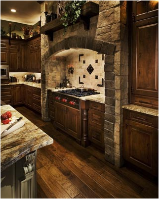 A Kitchen With An Recessed Area For The Stove Decorated With Stone - Old World Kitchen Design