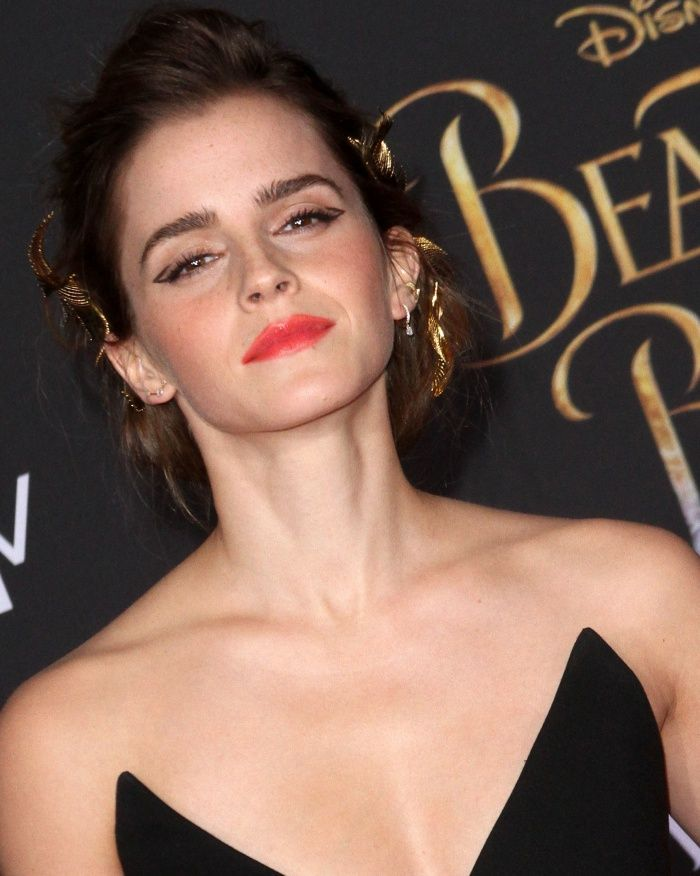 Emma Watson's hair was styled in a loose updo adorned with ...