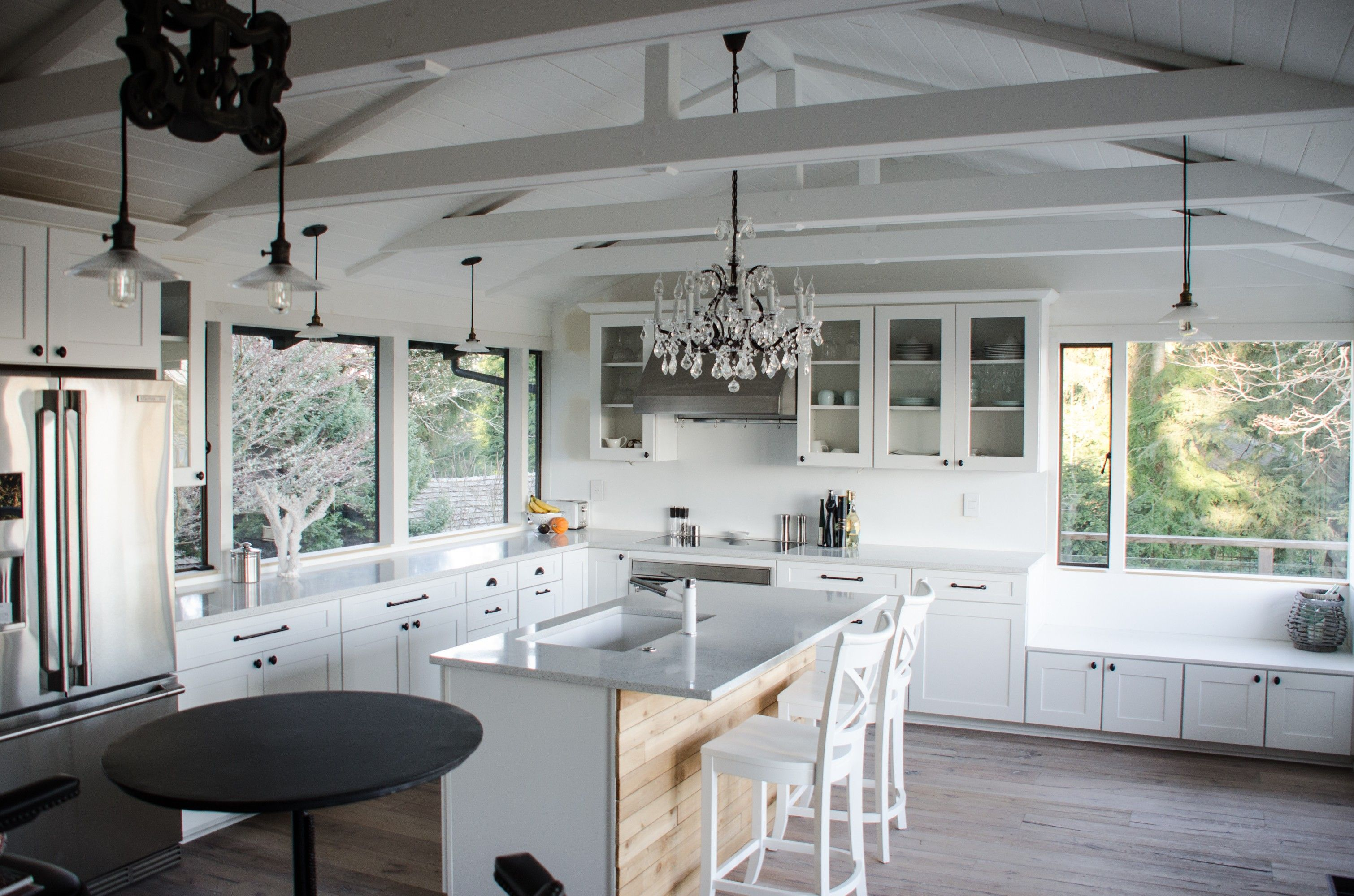 White kitchen with a chandelier great contract with more rustic