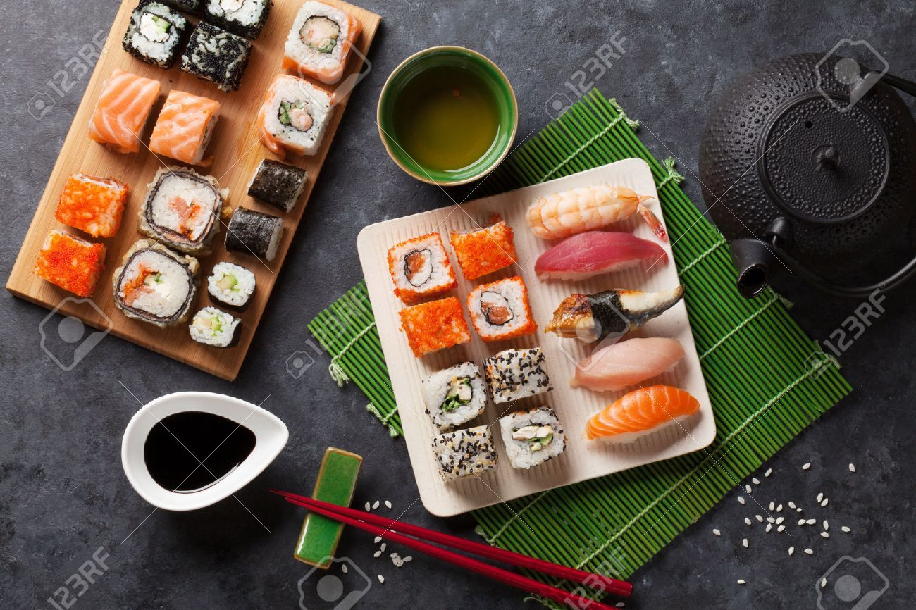 Set of sushi and maki roll and green tea on stone table
