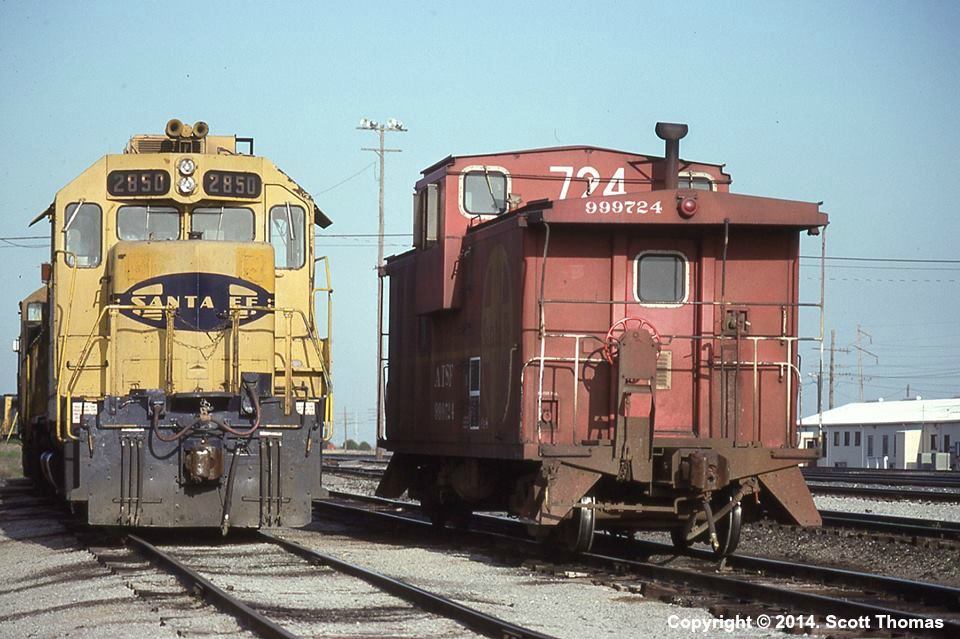 ATSF #2850, an EMD GP35, and an extended vision caboose, ATSF #999724, enjoy a moment of tranquility at Wellington, KS on 04 April 1992.  Photo by Scott Thomas.