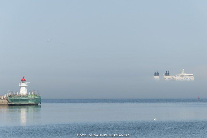Dimma över vatten där en båt tycks sväva