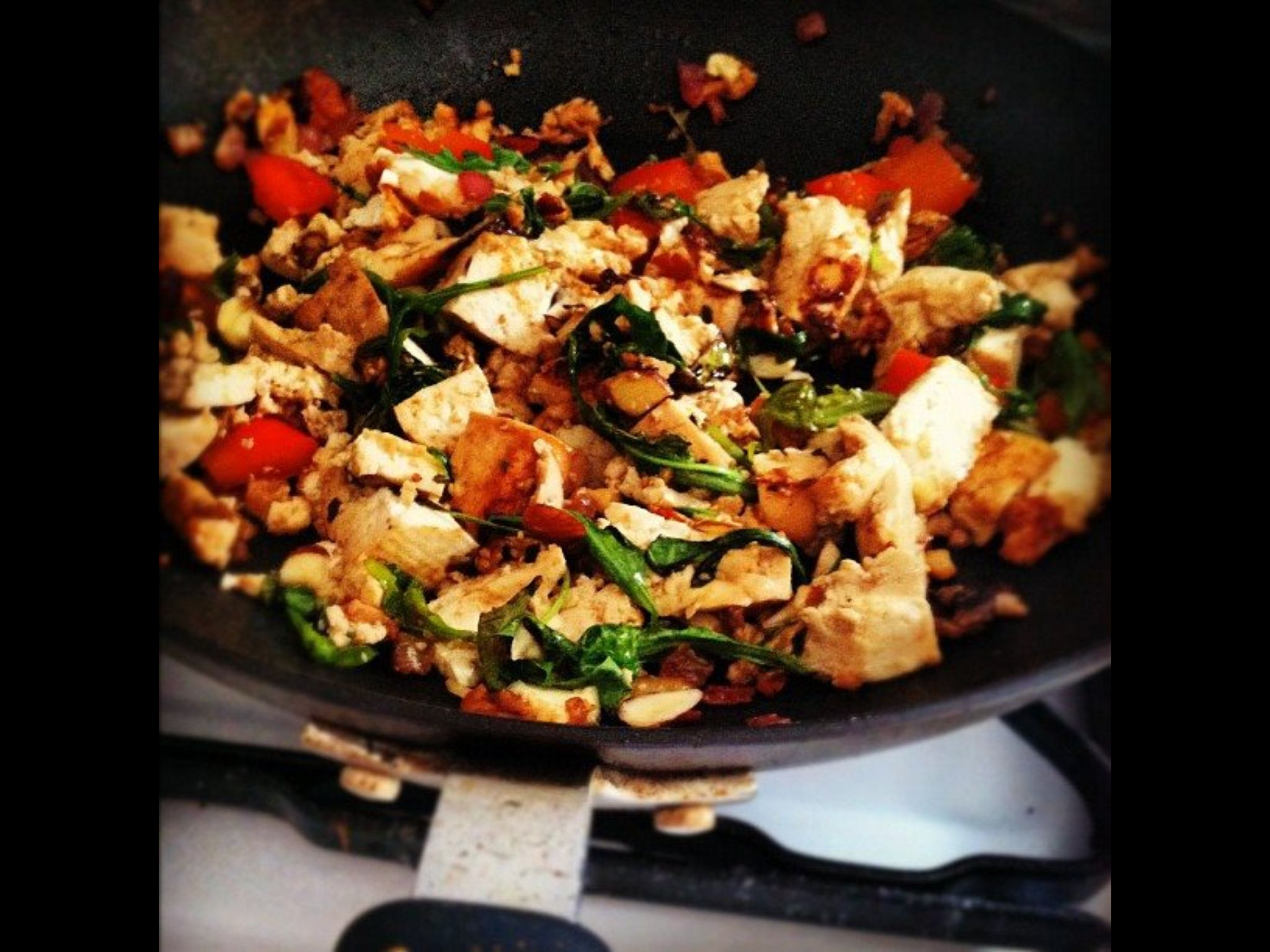 Scrambled Tofu. The perfect breakfast. Pan-fried ginger tofu with wilted arugula, red onions, garlic, roasted red peppers, basil, honey roasted walnuts with a hint of basil, pepper and turmeric seasoning. (For some more flavor add nutritional yeast, and soy sauce)
