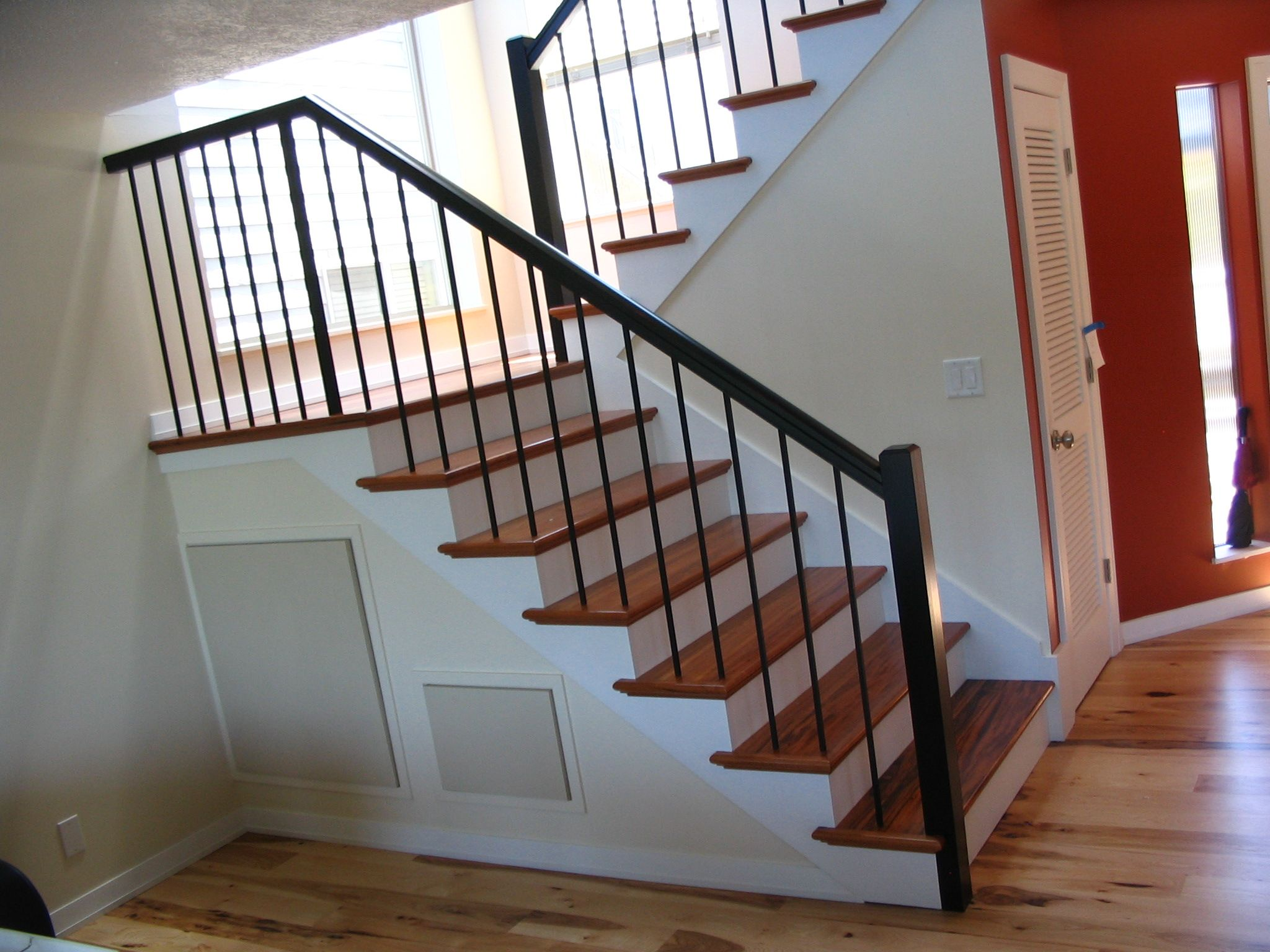 Contemporary stairs, Tigerwood treads, plain wrought iron balusters posts,