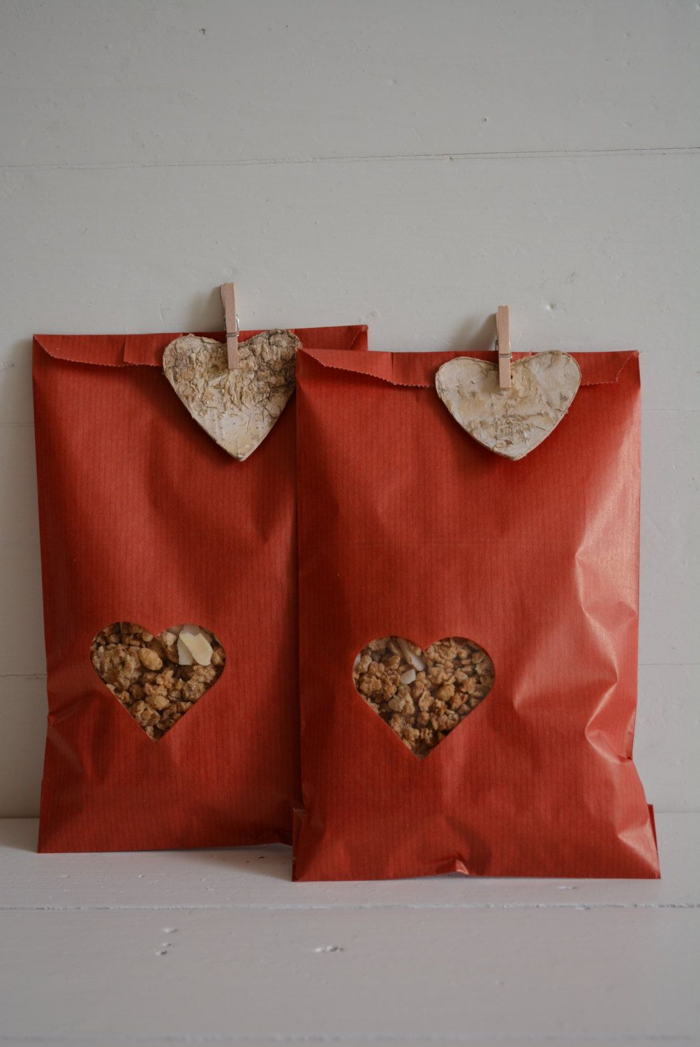 bundle of 100 red kraft paper bags with a small off center heart