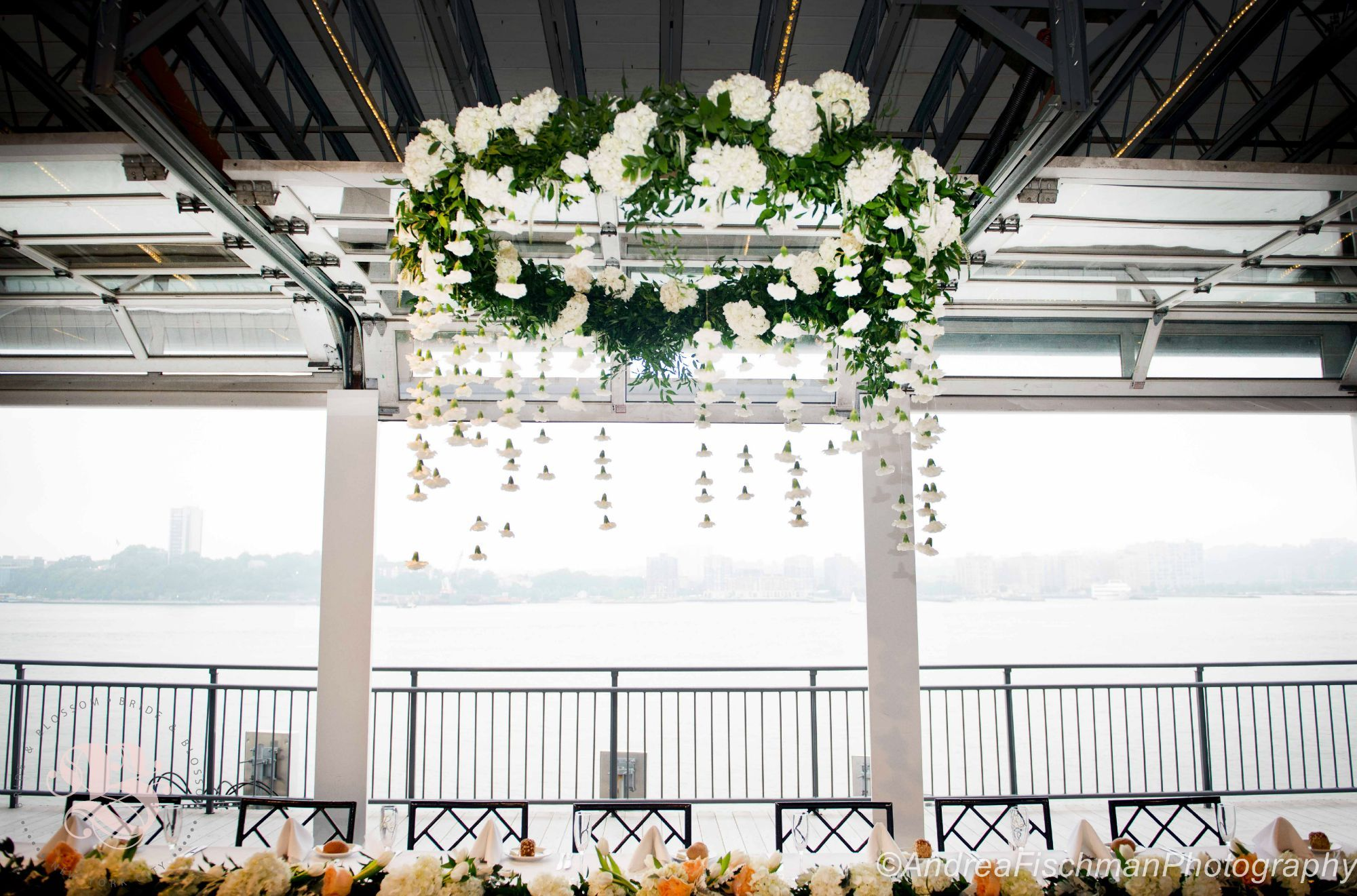 Floral Chandelier, suspended over head table with floral runner. Summer wedding, on the Sunset Terrace at Chelsea Piers in Manhattan. What could be more romantic than hanging florals? White flowers appear to float in air... Photo by Andrea Fischman #floralchandelier