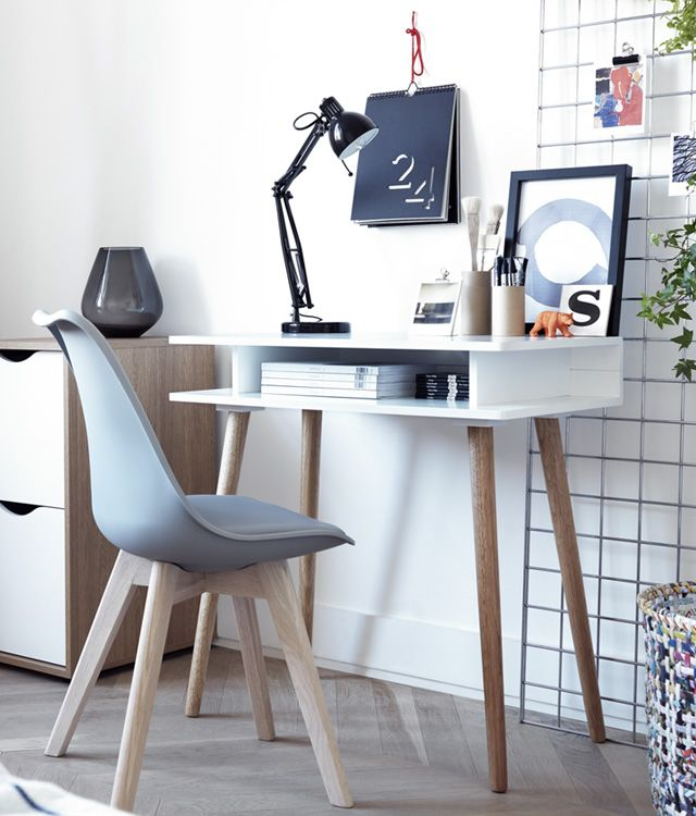 A White Desk With Blonde Wood Legs And A Grey Bucket Style Chair