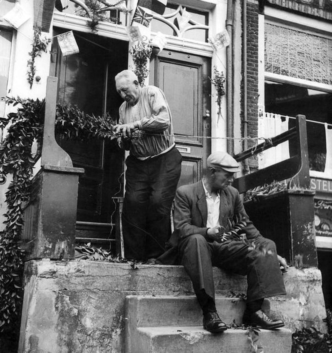 Two elderly Dutch men anticipate the arrival of Allied forces in Amsterdam by decorating their stoop. An armistice between the Germans and the Allies was signed on 4 May 1945 in Wageningen. A day later, the German garrison would unconditionally surrender in the Netherlands. However, some German pockets of resistance remained; on 7 May 1945, two days after German capitulation in the Netherlands, thousands of Dutch civilians were waiting for Canadian troops to arrive at Dam Square in…