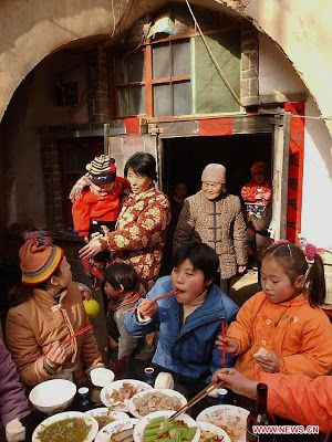 A family gather to have a family-reunion dinner outside their cave dwelling in Qucun Village of Shaanxian County, Henan Province, Feb. 1, 2003. Different from the other parts of China in which people have family reunion dinner on the Chinese New Year's eve, people living in the central China region have the family banquet at the noon of the first day of the lunar month. Chinese people who live in the central China region have formed various traditions to celebrate the Chinese Lunar New Year.
