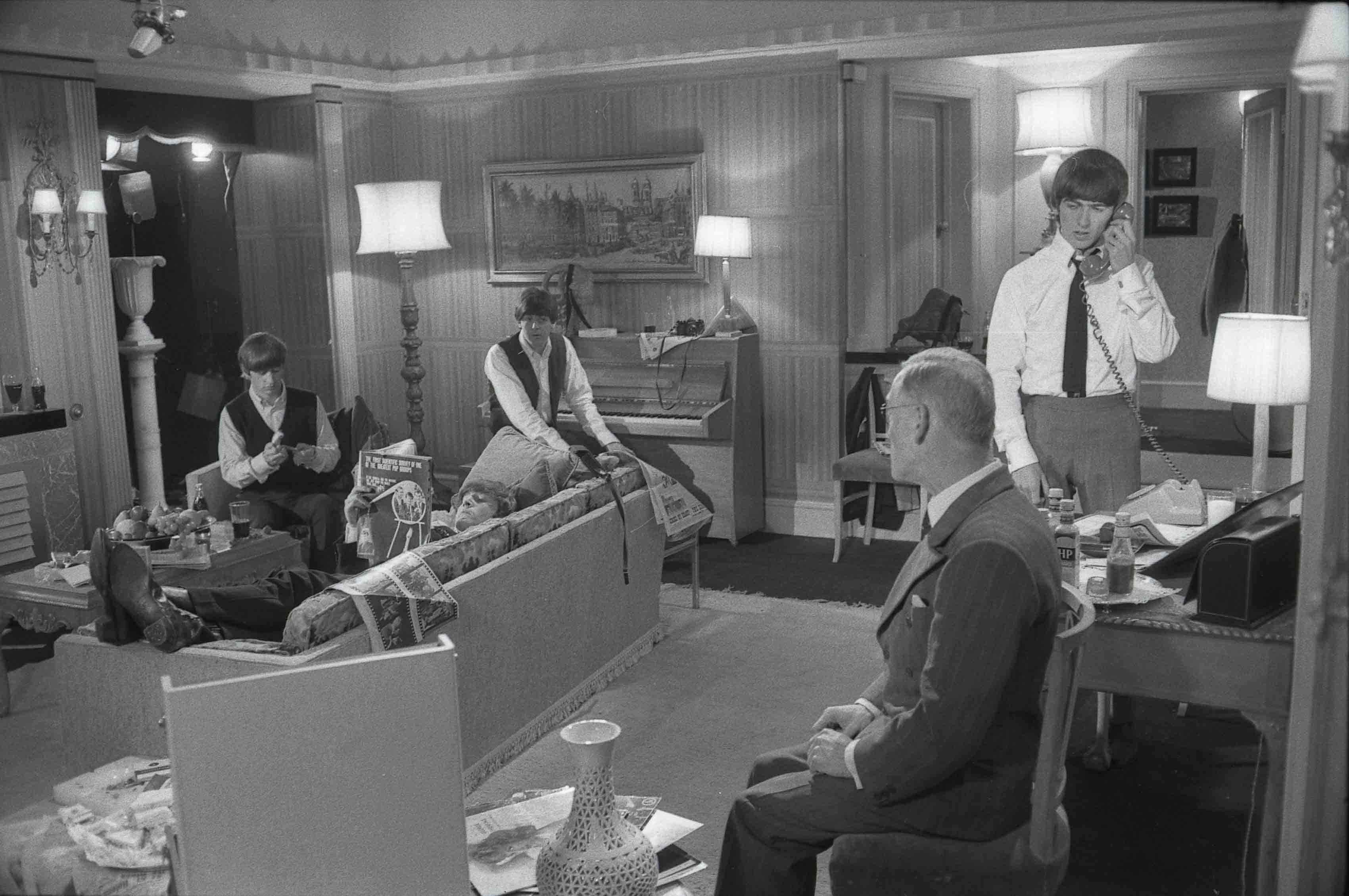 The Beatles waiting in a hotel suite in a still from 'A