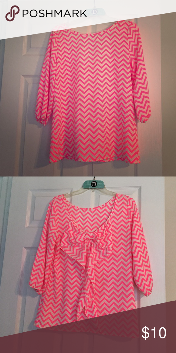 Neon pink and white  quarter length sleeve tunic Neon pink and white chevron quarter length sleeve tunic. This shirt has a scoop back accented with a cute bow.  100% polyester Auditions  Tops Tunics
