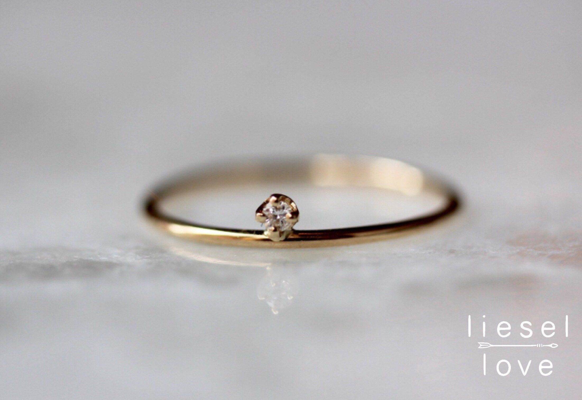 Simple, classic and oh-so-cute! Our tiny floating diamond ring stacks well with other rings, and also looks great as a midi ring! - Handcrafted out of 14K yellow, white or rose gold - Diamond measures 1.7mm, conflict free - Band is approximately 1.3mm in width Processing times - Current processing time is 1 - 3 weeks. Each Item is handmade to order with love and care! In Stock Items - Contact Liesel Love with any rush order questions, or to see if we have anything ready made and in stock. Return