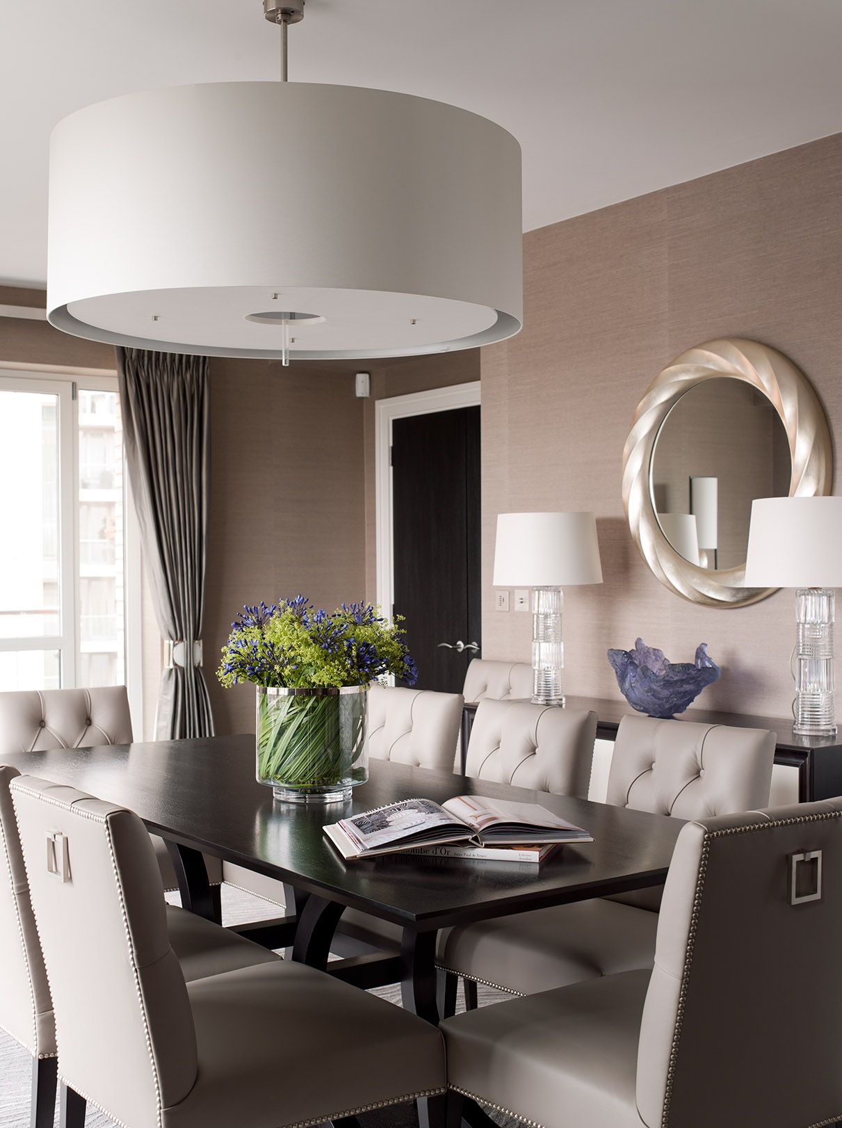 Eight Off White Tufted Chairs Surround A Dark Wood Table In This Chic  Transitional Dining Room. A Dark Blue Accent Wall Attracts The Eye To The  Buiu2026