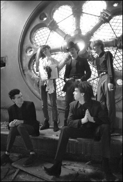 The Birthday Party : Nick Cave , Rowland S. Howard , Mick Harvey , Tracey Pew and Phill Calvert in disused church in Kilburn photographed by David Corio .