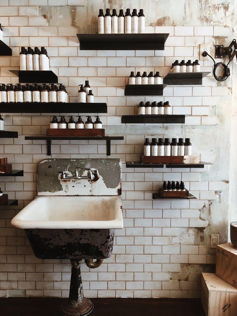 Bottles on wall shelves above sink store pinterest skin care