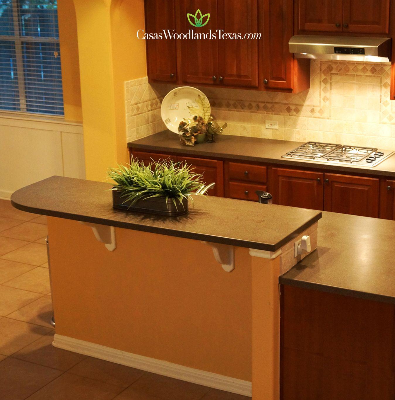 Su cocina cuenta con una amplia isla, gabinetes de madera y encimeras de granito. #Hogar #Casas #Interiores