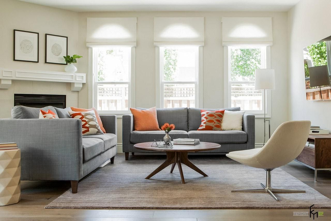 An inspiring living room design with amusing round wooden table and grey sofa with astounding orange patterned cushions and sweet elegant cream chair