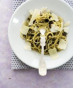 Spaghetti met olijvenpasta  (6-4pers)     400g spaghetti  zout, vers gemalen peper  200g zwarte olijven (goede kwaliteit) zonder pit, fijngesneden  3 teentjes knoflook, geperst  2tl gedroogde oregano of 3 takjes verse oregano  50 g gepelde amandelen, helft fijngemalen, helft grof gehakt  2el extra vierge olijfolie (+ extra)  Parmezaanse kaas, geschaafd (of zwarte truffel, in flinters)  extra nodig: keukenmachine of vijzel
