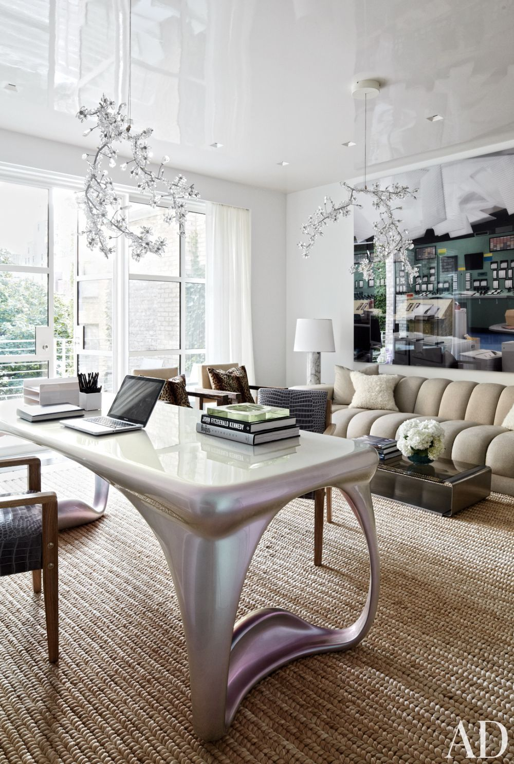 In the study of a New York townhouse, Studio Tord Boontje for Swarovski chandeliers overlook a Vladimir Kagan sofa clad in a Clarence House#interiordesign
