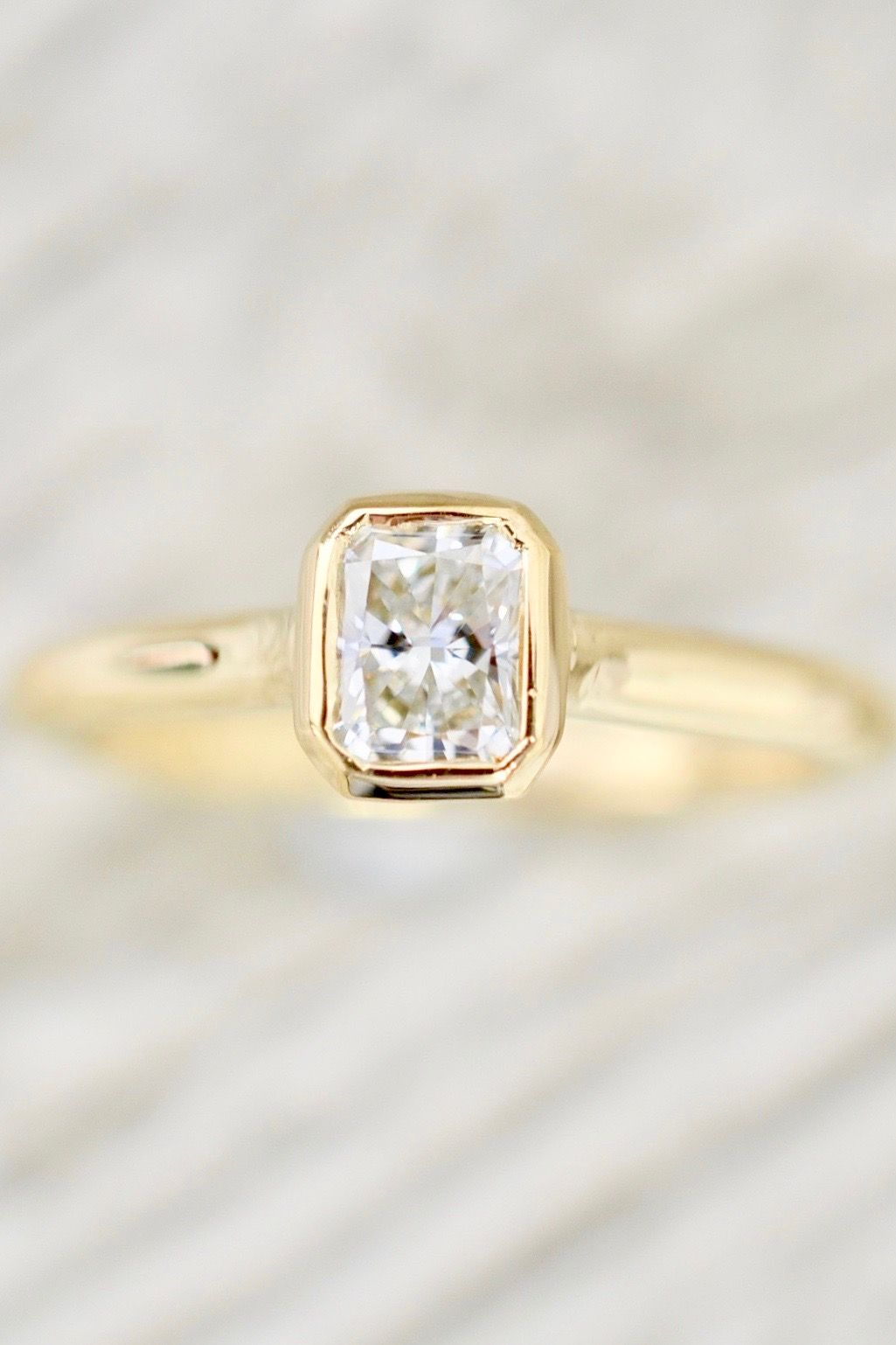 Radiant cut diamond in a bezel set open gallery solitaire engagement