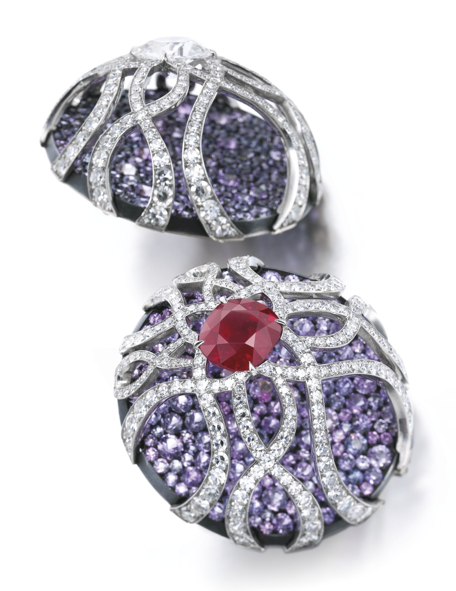 Pair of superb sapphire, ruby and diamond earrings, JAR Each of circular form, pavé-set with circular-cut sapphires of various hues ranging from light pink to purplish blue, surmounted with a stylised cage set with a cushion-shaped stone, one a diamond weighing 3.06 carats, the other a ruby weighing 4.89 carats, and lines of single-cut diamonds, signed JAR, French import marks, post and hinged back fittings, case by JAR.