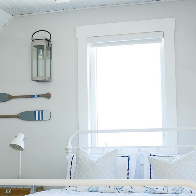 Pretty coastal style bedroom with oar wall decor.  #coastalliving #coastaldecor #coastalvibe #paddledecor #oardecor #lakehousedecor #lakehousevibes
