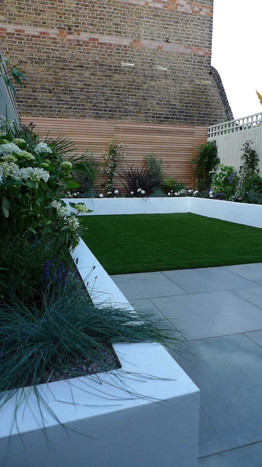 sawn grey sandstone paving raised rendered beds hardwood screen ...