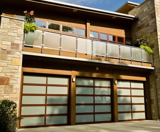 A Modern Two Story Stone House Has A Three Car Garage With Faux