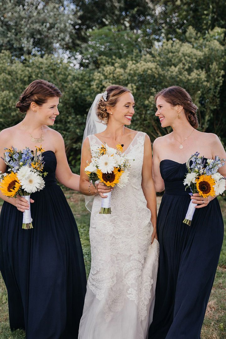 Bride and bridesmaids in navy blue dress and sunflower wedding bouquets for a backyard wedding | fabmood.com #wedding #backyardwedding #fallwedding #sunflowerthemed #weddingbouquets