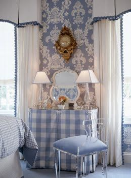 Blue bedroom by Kelley Proxmire with a vanity with a blue and white gingham skirt, blue and white damask wallpaper, vintage gold wall clock, white vintage mirror and a lucite chair