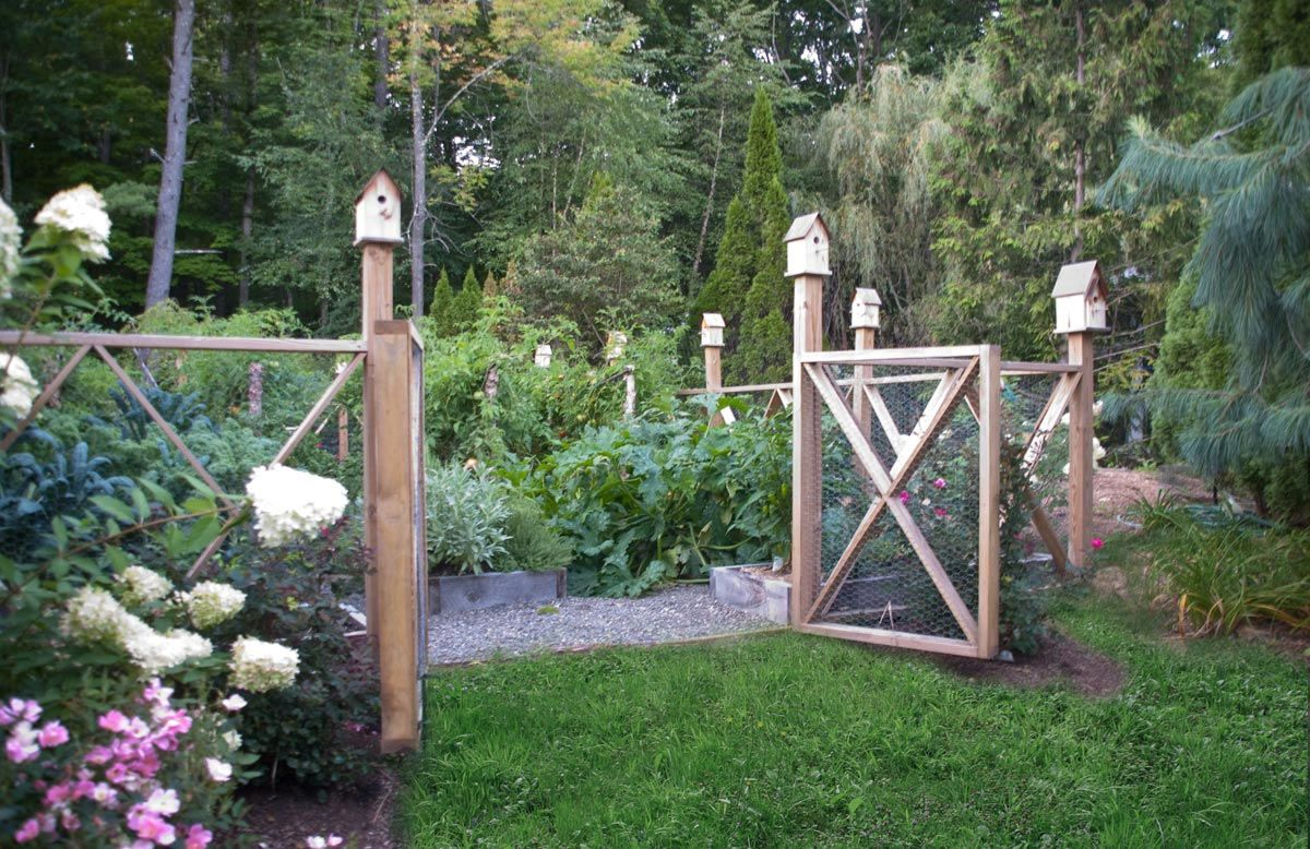 a cedar decorative fence and birdhouses surround an organic vegetable garden gayle burbank landscapes