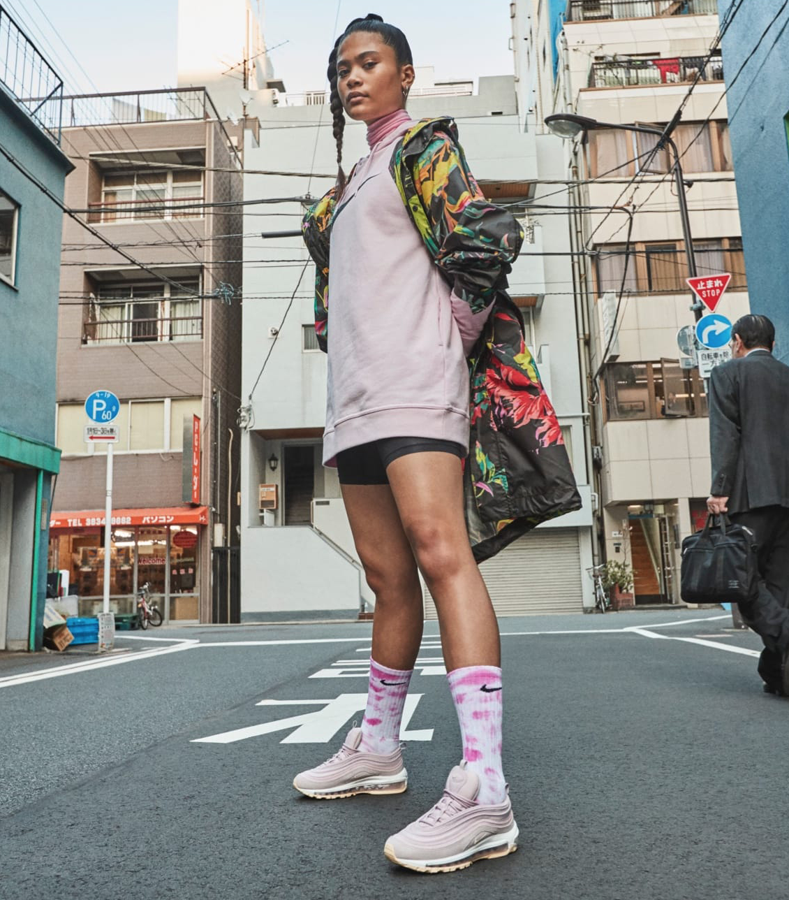 f5c48d7090b1e Girl wearing Nike Air Max 97 shoes in pink and white with Nike Sportswear  Pack 2019 collection clothing. Street style in Asia.