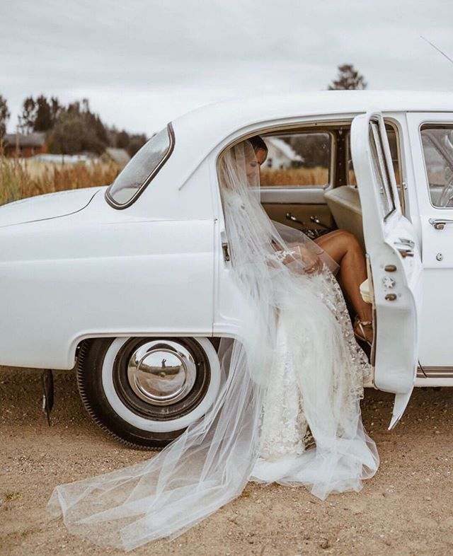 Bride getting ready to step out of a white vintage car. Vintage wedding car phot…