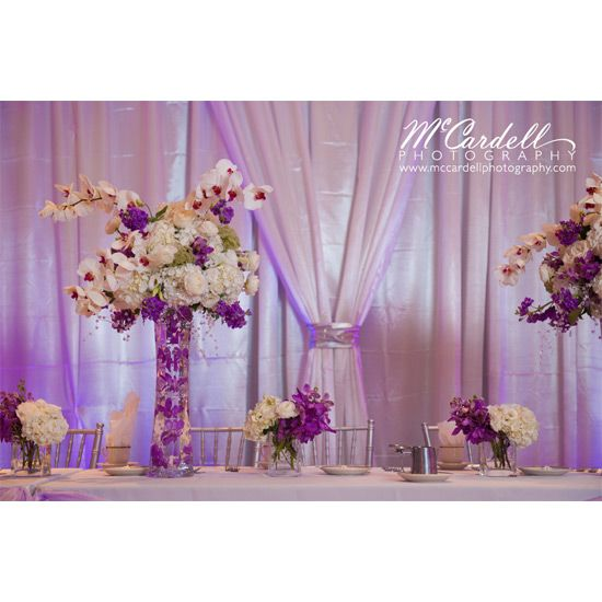 Elevated purple and white head table floral decor for Quinceanera celebration, using orchids, hydrangeas, stock, roses and accent flowers, by Eliana Nunes Floral Design.
