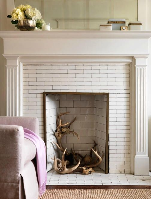 Non Working White Tile Fireplace Filled With Horns