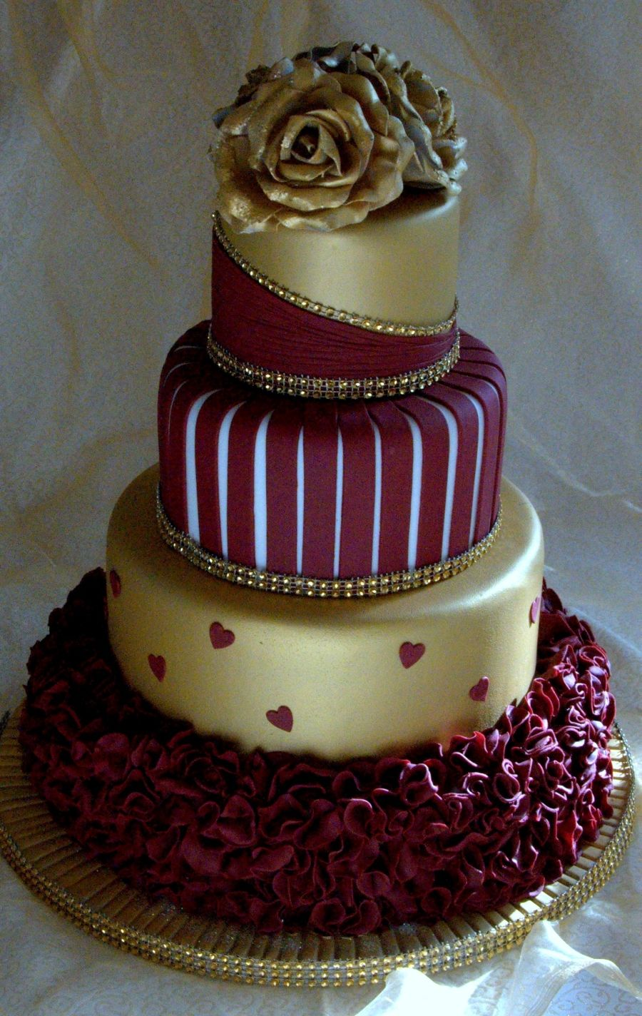 Gold and burgundy wedding cake with ruffles and roses