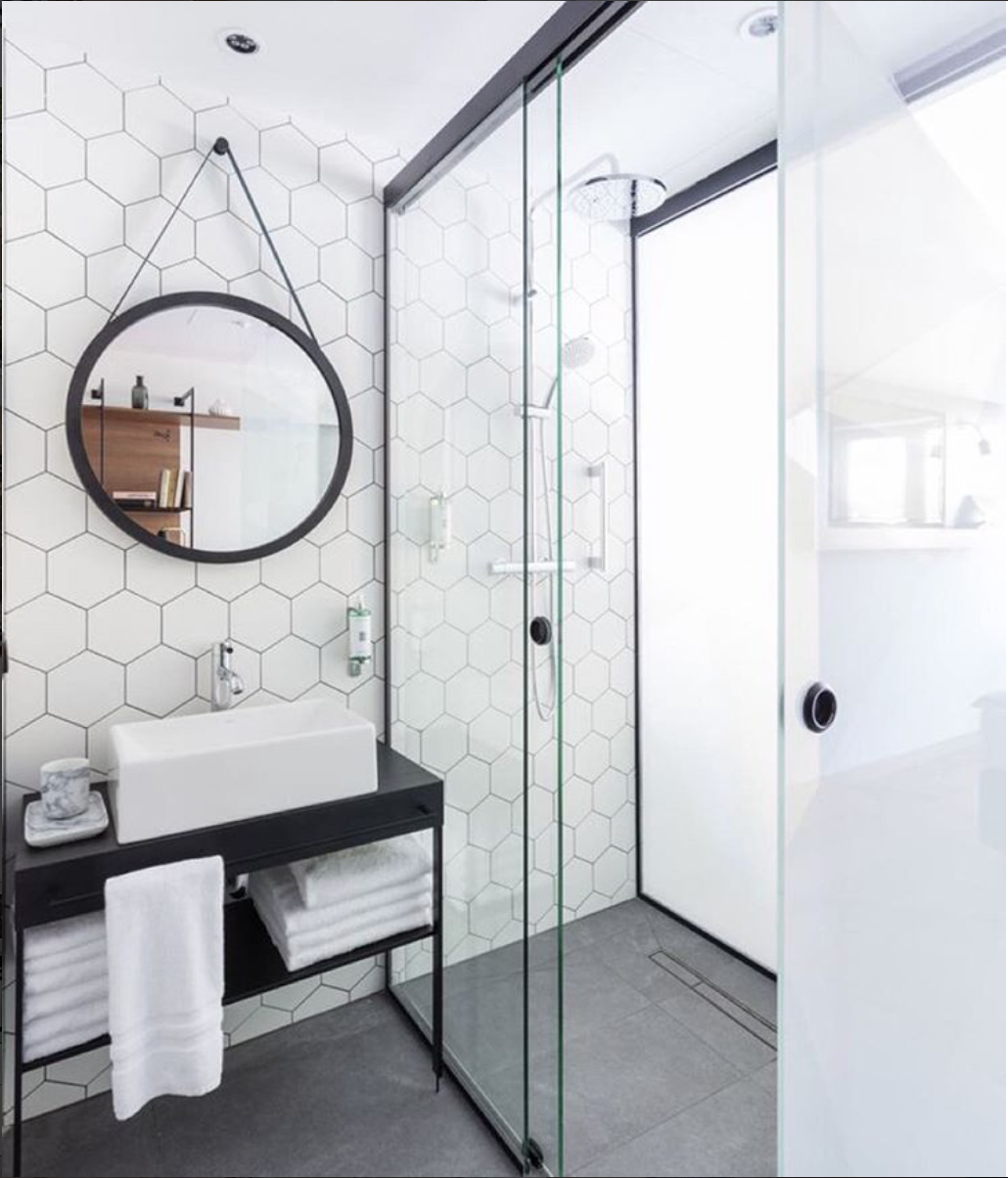 Modern Black Vanity With White Hexagon Wall Tile In Bathroom.