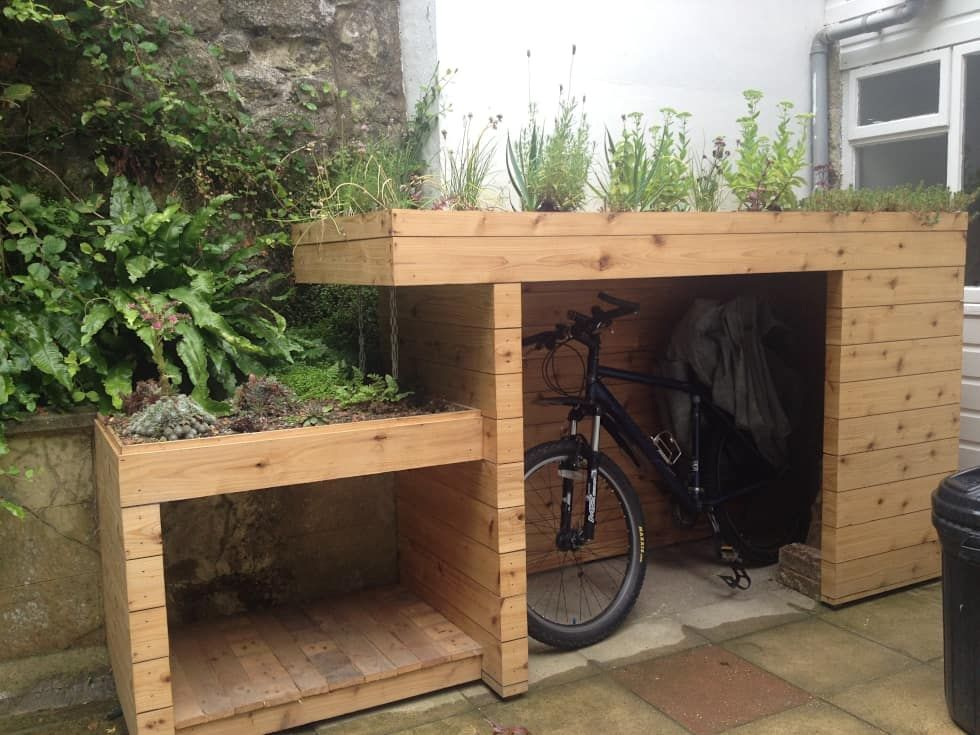 Simple Bike and log store with green roof modern Garden by Organic Roofs