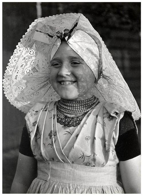Meisje uit Ovezande in rooms-katholieke Zuid-Bevelandse streekdracht. Ze is gekleed in opknapdracht. Over de ondermuts en de tussenmuts draagt ze een 'poepinnemuts' (meisjesmuts) 1950 #Zeeland #ZuidBeveland #katholiek