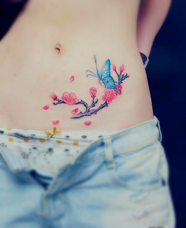 a tattoo showing butterfly flying around a flower