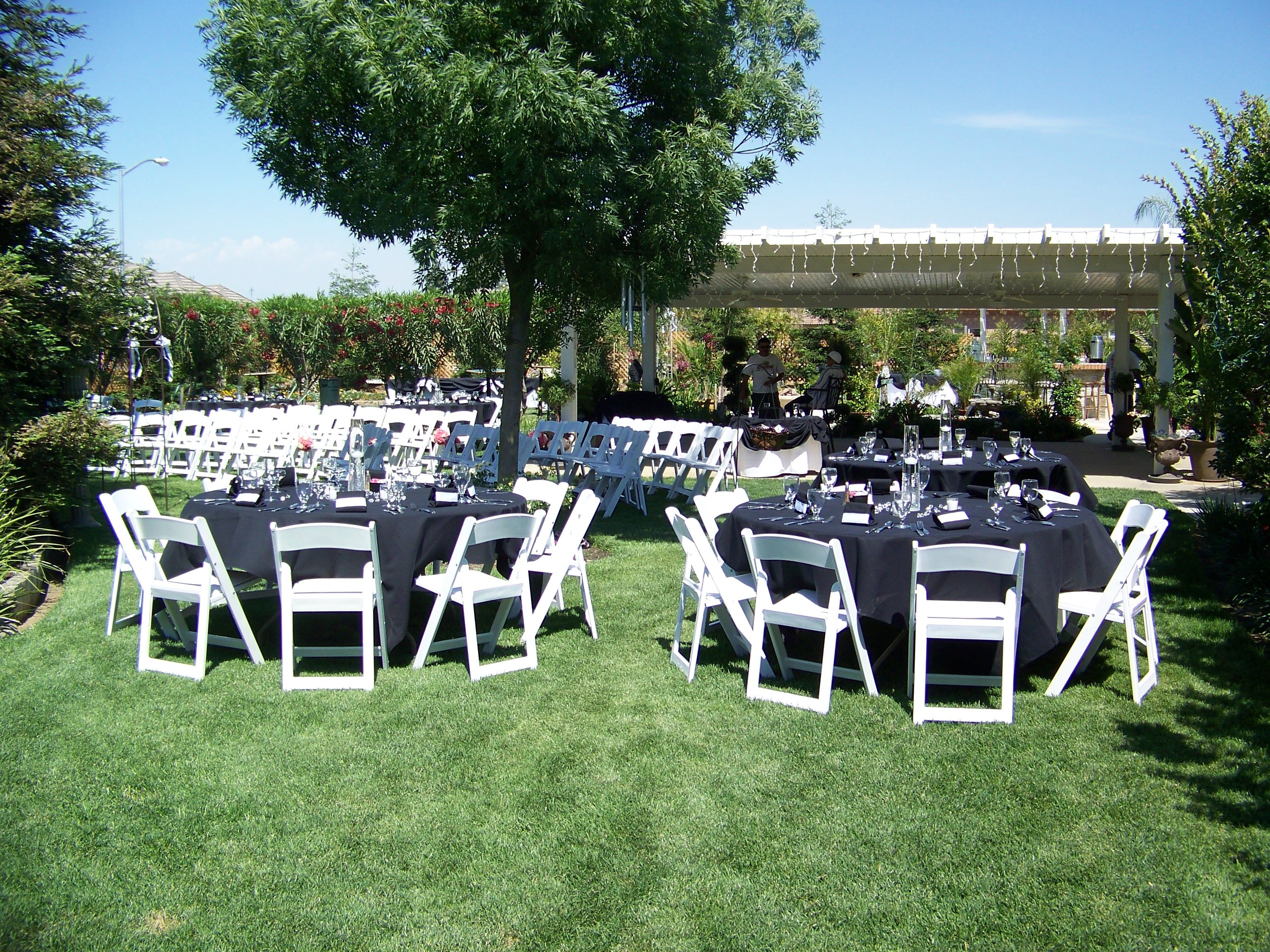 Black folding chairs wedding - Reception Layout In Backyard With White Padded Wedding Chairs