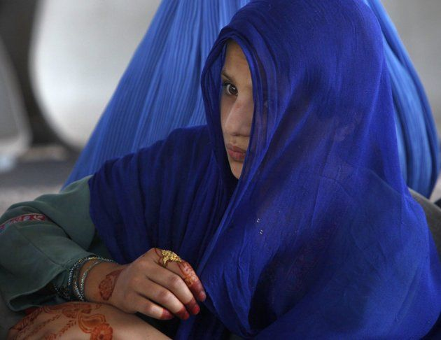 An Afghan woman sits while waiting to go back to Afghanistan from a United Nations funded repatriation centre in the western city of Peshawar, Pakistan. June 20, 2012.  Photo By FAYAZ AZIZ/REUTERS