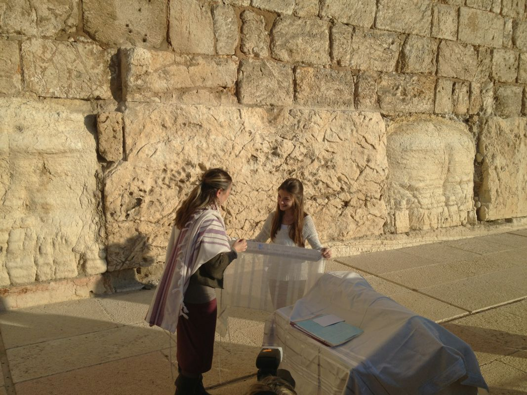 Bat Mitzvah at the Southern wall, A thirteen-year-old Jewish girl is standing in front of a wall her ancestors built two thousand years earlier, which was destroyed and rebuilt a dozen times before she was born. She holds a piece of cloth in her hands, made in Israel, purchased in America, and now brought back to Israel for this moment.