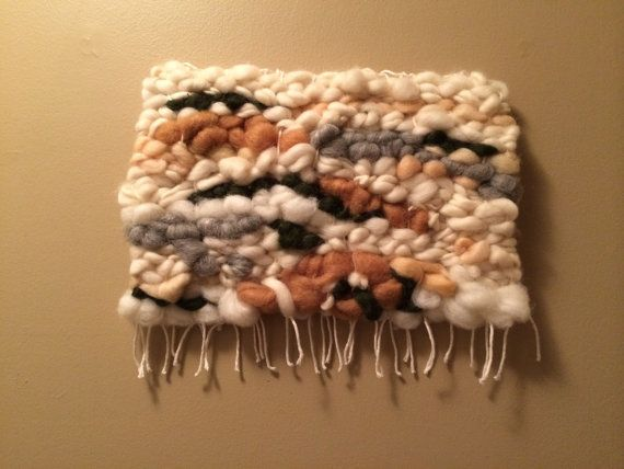 Handmade wall hanging using wool roving and alpaca. This piece is inspired by the colors and warm layers of Fall. Approximately 13 inches wide by 10.5