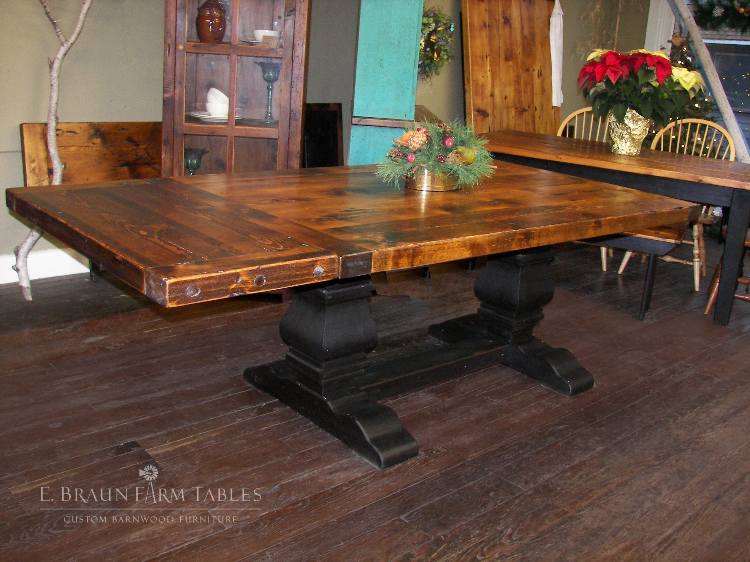 this 3 thick top low to medium character spruce reclaimed barn wood table has a black painted pear pedestal trestle base and is stained in dark tudor