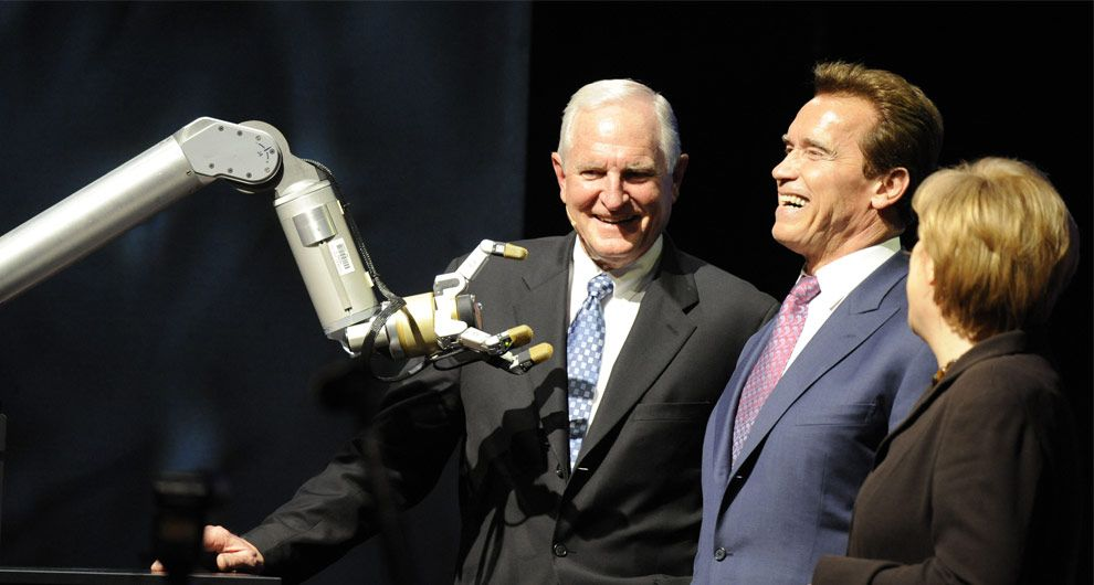 CEO of Intel Craig R. Barrett, California Governor Arnold Schwarzenegger and German Chancellor Angela Merkel react to a robotic arm during the opening ceremony of the world's biggest high-tech fair, the CeBIT, in Hanover on March 2, 2009. (NIGEL TREBLIN/AFP/Getty Images)