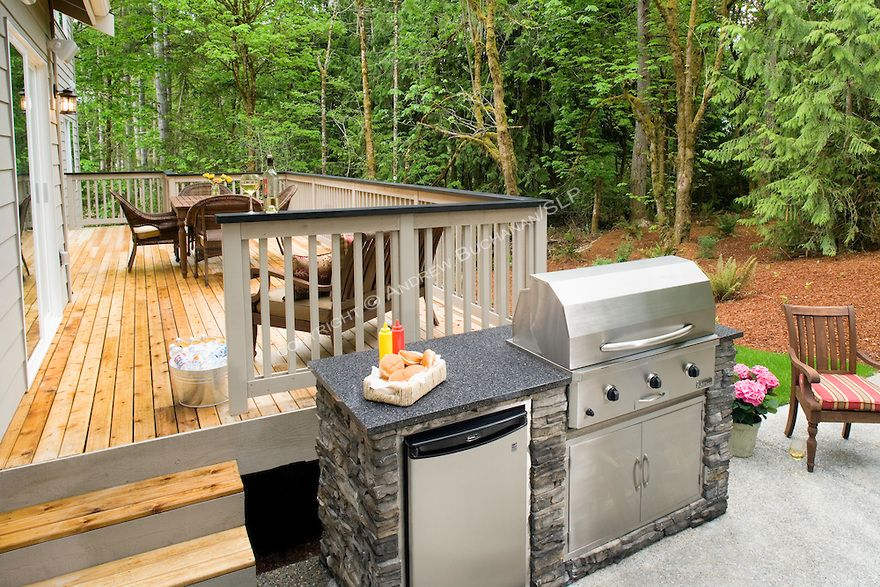 A Built In Stainless Steel Gas Grill And Refrigerator With A Granite Slab Worktop Sit Beside A Large Wooden Outdoor Refrigerator Outdoor Kitchen Outdoor Grill