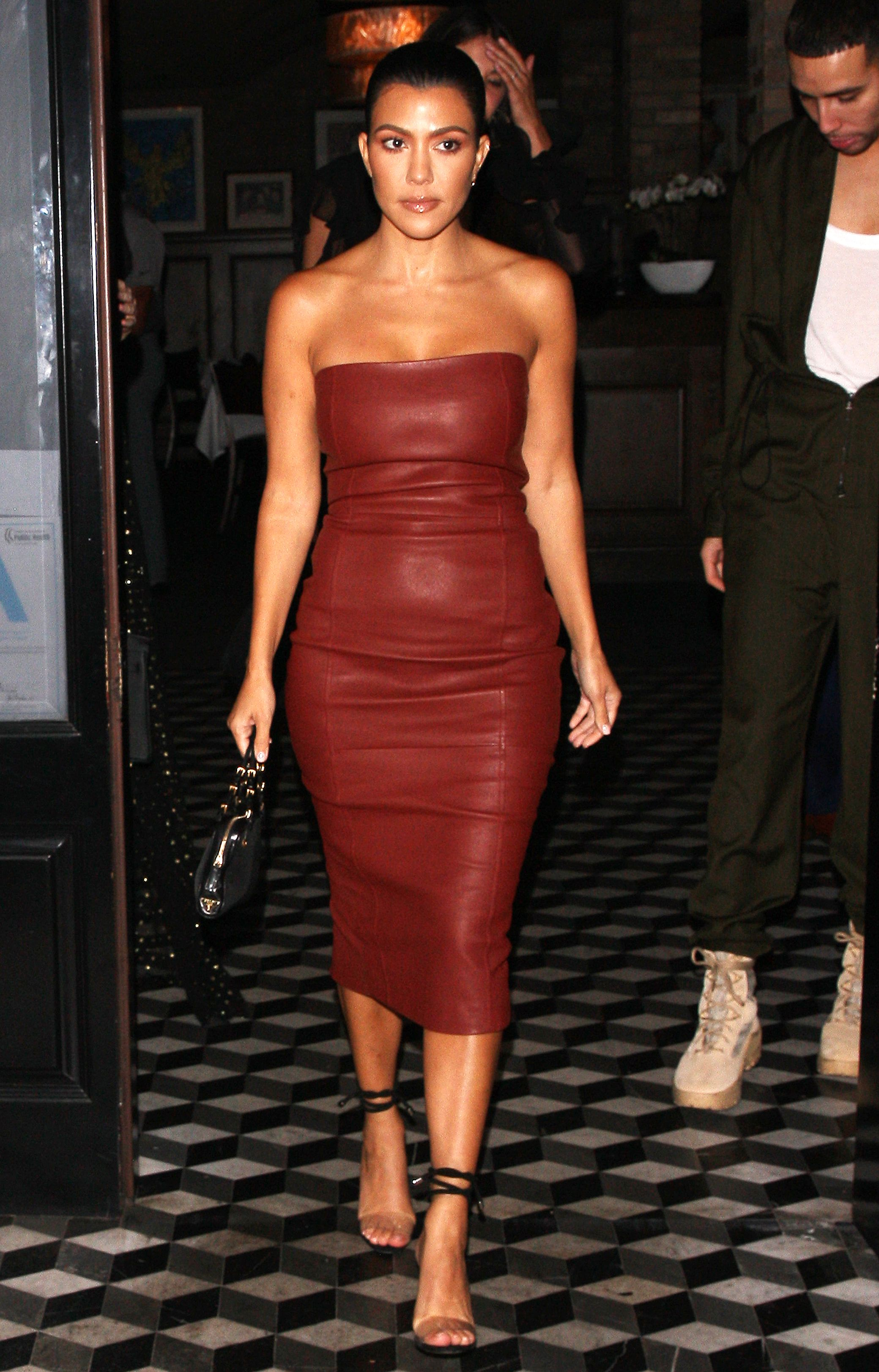 ac14677b2e39 Kourtney Kardashian in a strapless form-fitting midi, strappy heels and a  black handbag while leaving a dinner at Catch in L.A.