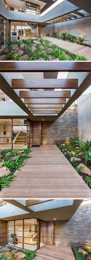 At the front of this modern house and off to the side, there's a wood walkway surrounded by plants and rocks, that leads to the front door. #Landscaping #Architecture #FrontEntrance #ModernHouse #WoodPath #CasaModerna #walkwaystofrontdoor